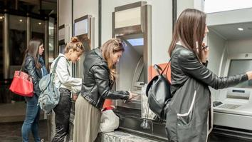 Four friends withdrawing money from an ATM at university