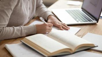Young girl preparing for university exams, writing coursework or essay